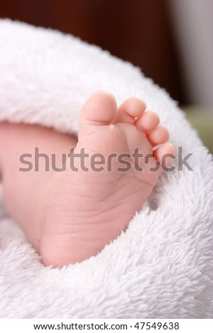 Beautiful uncovered toddler's foot on white blanket