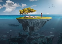 Beautiful underwater view of floating island above and below water surface in turquoise waters of tropical ocean with lone woman and marine life.