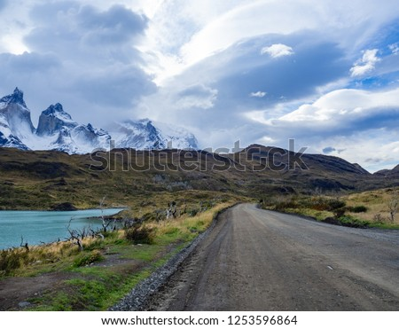 Beautiful unpaved road flanked by a lake on the way to Parque National Torres del Paine. Patagonia, Chile. #1253596864
