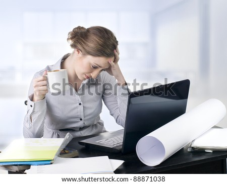 Beautiful upset businesswoman suffering from a headache in the office