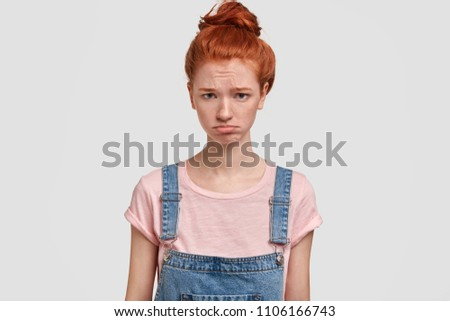 Beautiful upset ginger young female frowns face and looks offended, purses lips and has sorrowful gloomy expression, stands against white concrete wall. Displeased foxy teenager has problems