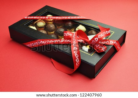 Beautiful Valentine closed black and gold box of delicious white, milk and dark chocolates in a black and gold box with romantic red heart ribbon on a red background.