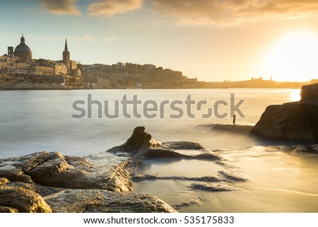 Beautiful Valletta skyline under a vibrant colorful golden sunset, long exposure with ghostly water across rock pools at Tigne Point, Valletta is the capital city of Malta, Europe