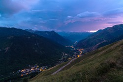 Beautiful valley with small typical mountain villages illuminated with the lights of the street lamps at sunset. Panoramic view of Valle de Aran, Baqueira-Beret, Salardú, Lérida, Catalonia, Spain.