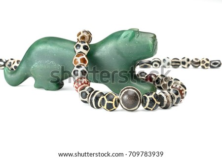 Beautiful valuable Pyu ancient round shaped etched agate and etched carnelian beads in necklace on big Nephrite Pyu tiger ancient bead on white background