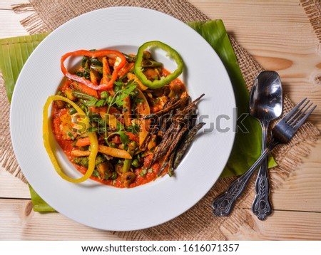 Beautiful vegetarian dish with a lot of colors on a white plate along with a fork and a spoon