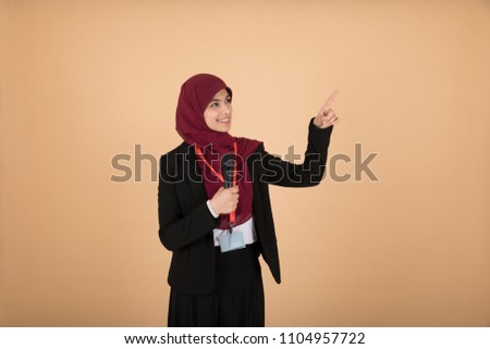 Beautiful veiled girl in a formal outfit holding a microphone pointing at something with one finger talking and giving a lecture on a beige background.