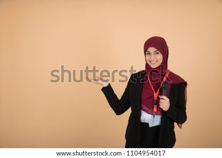 Beautiful veiled girl in a formal outfit holding a microphone pointing at something with one hand talking and giving a lecture on a beige background.