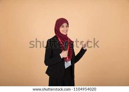 Beautiful veiled girl in a formal outfit holding a microphone talking and giving a lecture on a beige background.