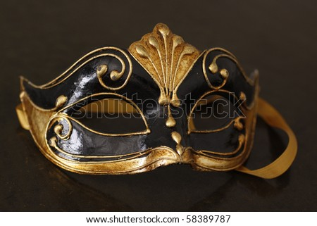 Beautiful Venetian mask in black and gold on top of an old leather table.