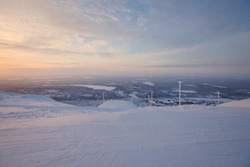Beautiful vibrant sunny scandinavian lapland winter aerial landscape with slopes, skiing resort and cottages