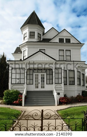 Beautiful Victorian white house with a lawn in front - stock photo