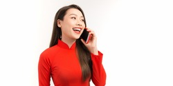 Beautiful vietnam women wearing Ao Dai vietnam traditional dress standing and talking on smartphone isolated on white background.