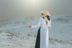 Beautiful vietnamese lady with vietnam culture traditional dress standing at a white sand Mui ne, Ho Chi Minh City Vietnam