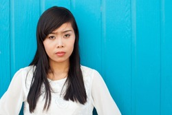 Beautiful vietnamese woman standing near colorful blue wooden wall. Copy space.