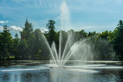Beautiful view across a pond in a park in Sweden. With a fountain squirting water up in the air. Backlight from the sun makes the water shine