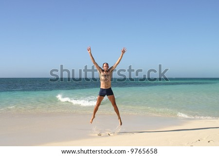 Beautiful view at sandy beach with one guy jumping with arms raised. Australia.