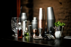 beautiful view composition with different bar equipment and steel tools which stand on bar counter.