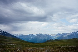 Beautiful view from mountain pass to great snowy mountains under cloudy sky. Dramatic alpine landscape with snow mountains in rainy weather. Gloomy scenery with giant mountain ridge in overcast day.