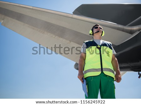 Beautiful view. Low angle portrait of airport worker. Man holding clipboard and looking up with calmness #1156245922