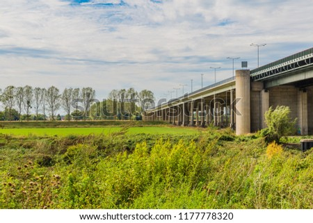 beautiful view of a concrete bridge over a field with green grass and trees near Elsloo and Meers South-Limburg in the Netherlands Holland #1177778320