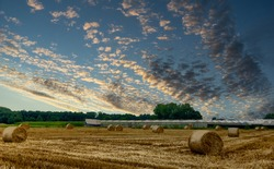 Beautiful view of a dramatic sunset sky over harvested hay field with hay bales in the Kempen area, Belgium