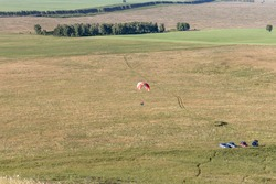 Beautiful view of a pilot with red and white paraplane flaying over green and yellow fields in summer in the morning