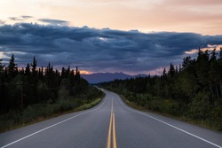 Beautiful View of a scenic road, Alaska Hwy, in the Northern Rockies during a dramatic cloudy sunset. Taken in British Columbia, Canada. Nature Background