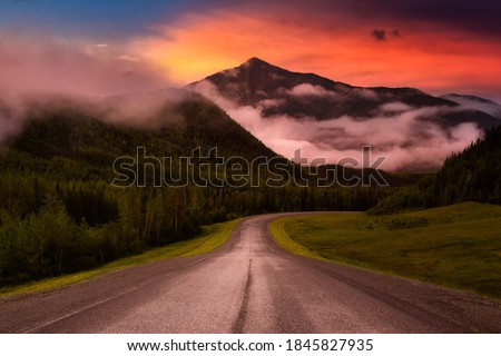 Beautiful View of a scenic road, Alaska Hwy, in the Northern Rockies during a sunny and cloudy morning sunrise. Dramatic Sky Artistic Render. Taken in British Columbia, Canada. Nature Background Foto stock ©