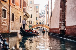 Beautiful view of a small canal in Venice with gondolas