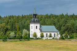 Beautiful view of a white church on the Swedish countryside with a green forest in the back and bright summer sunlight