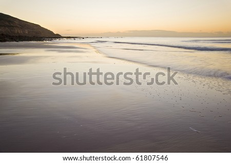 Beautiful view of beach at sunrise with rock details