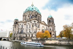 Beautiful view of Berliner Dom (Berlin Cathedral) at famous Museumsinsel (Museum Island) with excursion boat on Spree river in beautiful evening light at sunset Berlin. Germany..