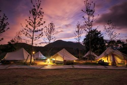 Beautiful view of canvas glamping bell tents in a green field with walhway at moutain in beautiful sky with cloud before sunrise.