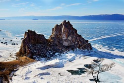 Beautiful view of Cape Burhan or Shamanka rock on Olkhon island in winter. Frozen lake Baikal, transparent smooth ice.