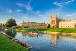 Beautiful view of college in Cambridge with people punting on river cam