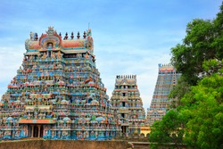 Beautiful view of colorful gopura in the Hindu Jambukeswarar Temple against the background of cloudy blue sky in Trichy (Tiruchirapalli), Tamil Nadu, South India
