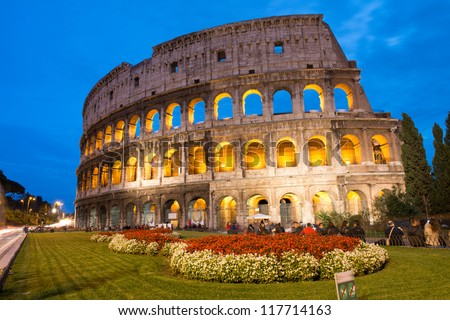 Beautiful view of Colosseum at sunset with flowerbed in foreground - Rome - Italy - stock photo