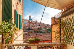 Beautiful view of Dome and campanile of Siena Cathedra, and Old Town of medieval city of Siena in the sunny day through autumn leaves, Tuscany, Italy