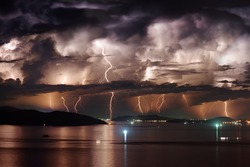 Beautiful view of dramatic dark stormy sky and lightning over Nha Trang Bay of South China Sea in Khanh Hoa province at night in Vietnam. Nha Trang city is a popular tourist destination of Asia.