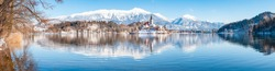 Beautiful view of famous Bled Island (Blejski otok) at scenic Lake Bled with Bled Castle (Blejski grad) and Julian Alps in the background in idyllic morning light at sunrise in winter, Slovenia