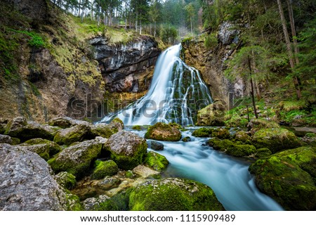 Beautiful view of famous Gollinger Wasserfall with mossy rocks and green trees on a moody in springtime, Golling, Salzburger Land, Austria