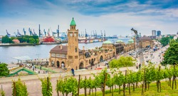 Beautiful view of famous Hamburger Landungsbruecken with commercial harbor and Elbe river with blue sky and clouds in summer, St. Pauli district, Hamburg, Germany