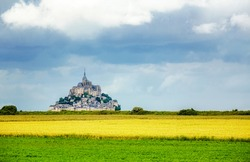 Beautiful view of famous historic Le Mont Saint-Michel tidal island in summer with yellow fields and meadows, Normandy, northern France
