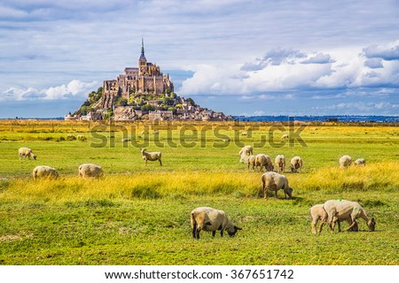 Stock Photo Beautiful view of famous historic Le Mont Saint-Michel tidal island with sheep grazing on fields of fresh green grass on a sunny day with blue sky and clouds in summer, Normandy, northern France