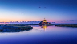 Beautiful view of famous Le Mont Saint-Michel historic tidal island in beautiful twilight during blue hour at dusk, Normandy, northern France
