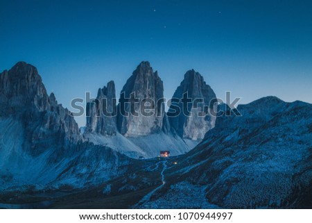 Beautiful view of famous Tre Cime di Lavaredo mountains in the Dolomites mountain range with famous Rifugio Antonio Locatelli alpine hut on a clear starry night in summer, South Tyrol, Italy