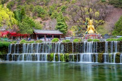 beautiful view of god of nature and waterfall stream outdoor flowing in jade village , lijiang , yunnan , China