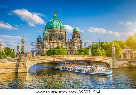 Beautiful view of historic Berlin Cathedral (Berliner Dom) at famous Museumsinsel (Museum Island) with excursion boat on Spree river in beautiful evening light at sunset in summer, Berlin, Germany #395071564