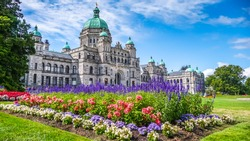 Beautiful view of historic parliament building in the citycenter of Victoria with colorful flowers on a sunny day, Vancouver Island, British Columbia, Canada